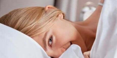 Une femme qui sourit dans son lit.