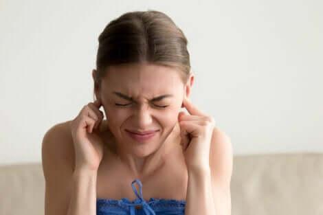 Une femme qui se bouche les oreilles.