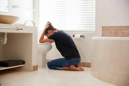 Une femme vomissant dans les sanitaires.