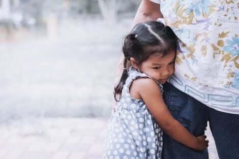 Une jeune fille qui s'accroche aux jambes de son papa.