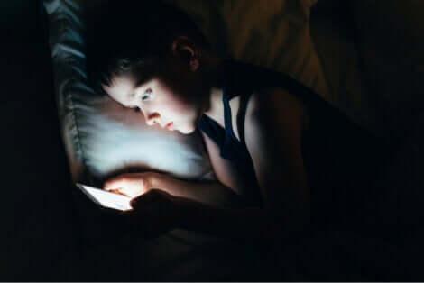 Une jeune fille qui regarde son téléphone au lit pendant la nuit.