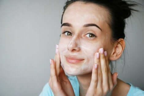 Une femme qui se met de la crème sur le visage avec des peptides.
