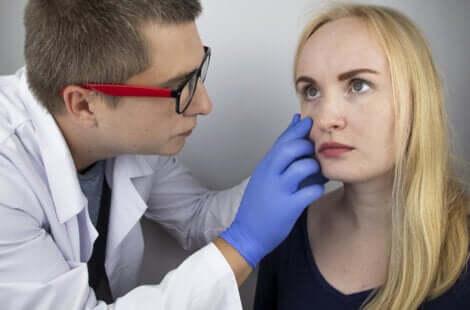 Un médecin qui ausculte les yeux d'une jeune femme.