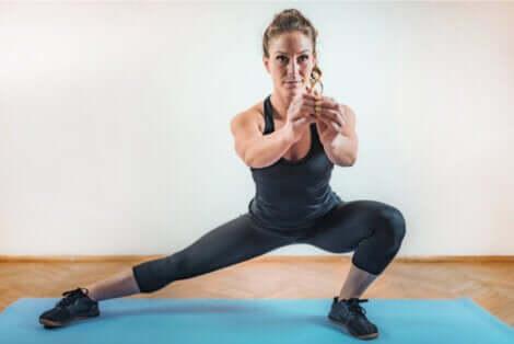Une femme qui réalise un squat latéral.