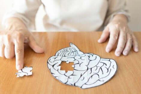 Une personne âgée qui fait un puzzle en forme de cerveau.