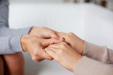 Quatre mains que se touchent de manière empathique.