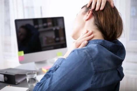 Une femme qui s'étire la nuque en travaillant devant l'ordinateur.