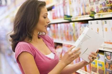 Une femme qui consulte un emballage alimentaire dans un magasin.