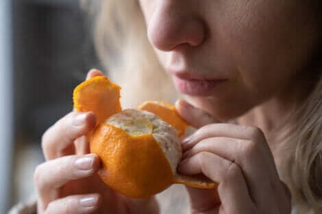 Une femme sentant une mandarine.