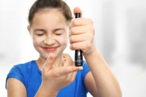 Une jeune fille qui prend sa glycémie à l'aide d'un stylo à insuline.