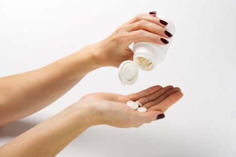 Une main qui verse des comprimés dans l'autre.