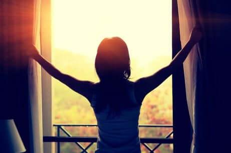 Une femme qui ouvre les rideaux.