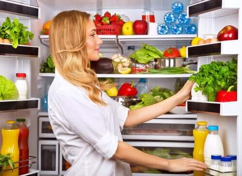 Une femme devant son réfrigérateur.