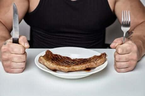 Un homme devant un morceau de viande.