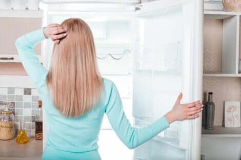 Une femme devant son congélateur.