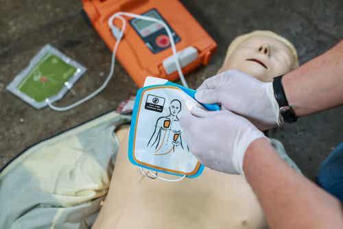 Un défibrillateur posé sur un mannequin.