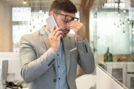 Un homme au bureau souffrant de fatigue visuelle.