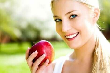 Une femme mangeant une pomme.