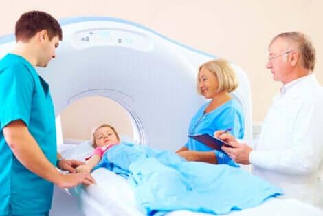 Un enfant avec une équipe médicale avant une tomographie assistée par ordinateur.