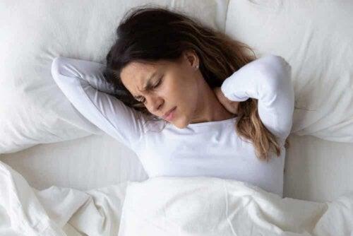 Une femme dans son lit souffrant de douleurs à la nuque.