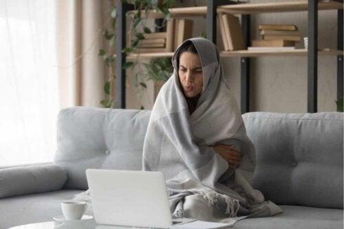 Une femme qui a froid dans son salon.