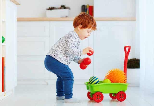 Un enfant rangeant ses jouets.