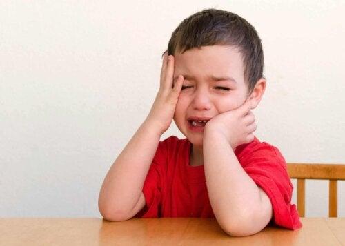 Un enfant qui pleure en se touchant la tête.