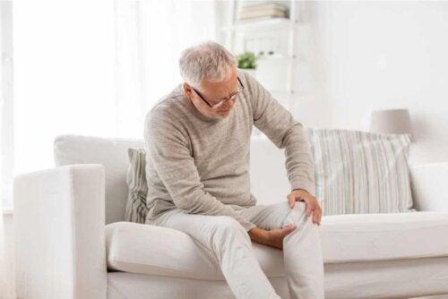 Un homme assis qui a mal au genou.