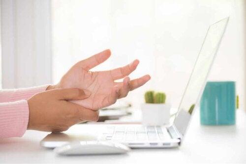 Une femme qui travaille et a mal à la main.
