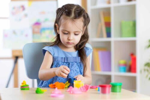 Une petite fille qui joue avec de la pâte à modeler.