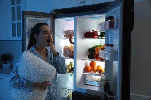 Une femme avec son oreiller devant son frigo en pleine nuit.