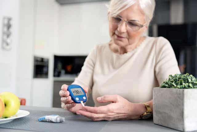 Une femme âgée mesurant son diabète.