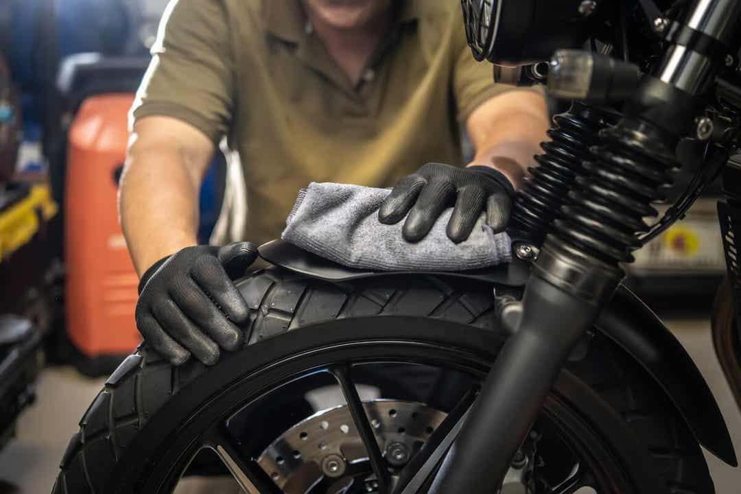Un homme qui nettoie une moto.