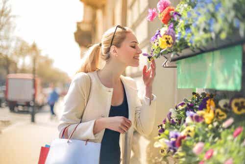 Femme qui renifle des fleurs.
