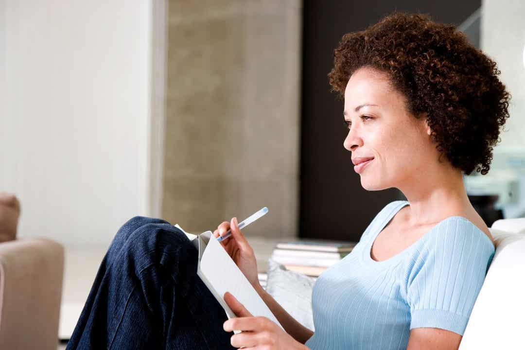 Une femme écrivant son journal de gratitude.