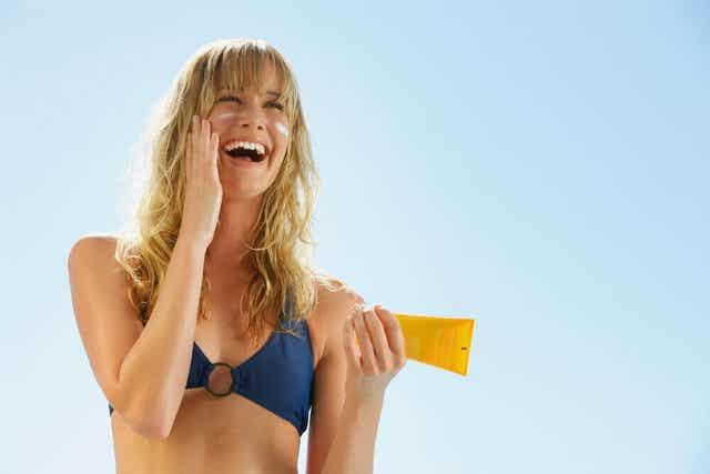 Femme qui met de la crème solaire.