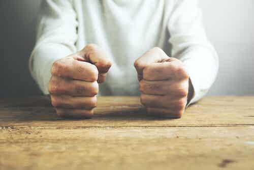 Des poings serrés sur une table.