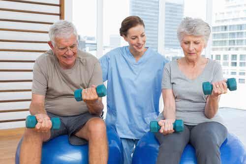 Deux personnes âgées qui font de l'exercice avec une soignante.